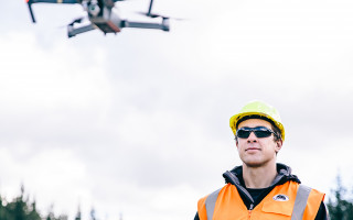 A man wearing a helmet and a hi-vis vest operates a drone