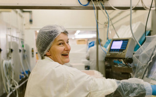 A lady wearing a hairnet smiles as she packs fish into boxes