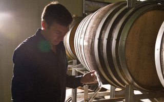 A man standing by wine barrels